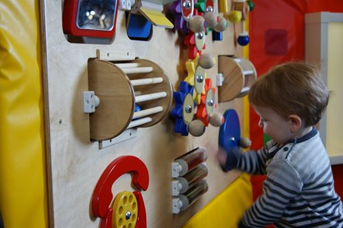 small child playing knobs and dials on a sensory wall